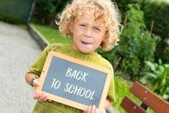 Kleiner blonder Junge, der eine Tafel hält Stockbilder