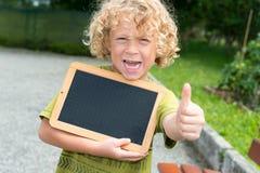 Kleiner blonder Junge, der eine Tafel hält Lizenzfreies Stockfoto