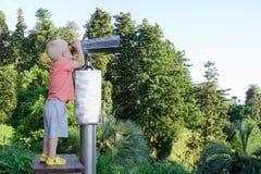 Kleiner blonder Junge, der in einem großen Paar Ferngläsern schaut Park im Hintergrund Lizenzfreie Stockfotos