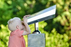 Kleiner blonder Junge, der in einem großen Paar Ferngläsern schaut Park im Hintergrund Stockbild