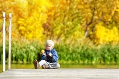 Kleiner blonder Junge, der einen Apfel auf dem Dock isst Herbst, sonnig Stockfotos
