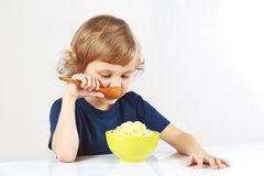 Kleiner blonder Junge, der einen Hirsebrei isst Lizenzfreie Stockfotografie