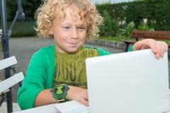 Kleiner blonder Junge, der einen Laptop, draußen verwendet Stockbilder