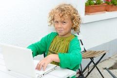 Kleiner blonder Junge, der einen Laptop, draußen verwendet Lizenzfreie Stockbilder