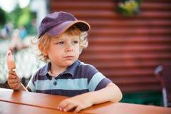 Kleiner blonder Junge, der Eiscreme im Sommer isst Lizenzfreies Stockbild