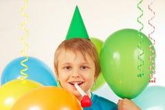 Kleiner blonder Junge in der Feiertagskappe mit Pfeife und festliche Ballone und Ausläufer Lizenzfreies Stockbild