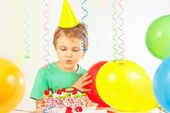 Kleiner blonder Junge in der festlichen Kappe, die Geburtstagskuchen betrachtet Stockfotografie