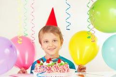 Kleiner blonder Junge in der festlichen Kappe mit Geburtstagskuchen und -ballonen Lizenzfreies Stockfoto