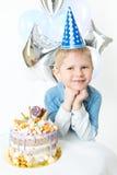 Kleiner blonder Junge in der festlichen Kappe, sitzen nahe bithday Kuchen Konzeptfeier Stockbild