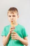 Kleiner blonder Junge, der frische Limonade durch ein Stroh trinkt Lizenzfreie Stockfotos