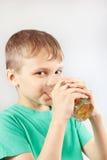 Kleiner blonder Junge, der frische Limonade trinkt Lizenzfreie Stockbilder