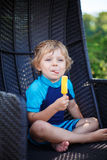 Kleiner blonder Junge, der gelbe Eiscreme isst Lizenzfreies Stockbild