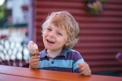 Kleiner blonder Junge, der gelbe Eiscreme isst Lizenzfreies Stockfoto