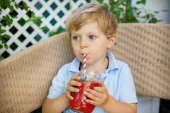 Kleiner blonder Junge, der gesunden Wassermelonensaft im Sommer trinkt. Stockbild
