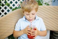 Kleiner blonder Junge, der gesunden Wassermelonensaft im Sommer trinkt Lizenzfreie Stockfotografie