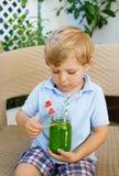 Kleiner blonder Junge, der gesunden Wassermelonensaft im Sommer trinkt Stockfoto