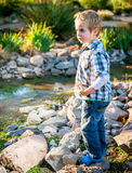 Kleiner blonder Junge, der im Garten spielt Lizenzfreie Stockfotos