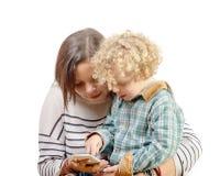 Kleiner blonder Junge, der mit dem Telefon seiner Schwester spielt Lizenzfreie Stockfotos