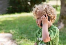 Kleiner blonder Junge, der mit einem Handy spielt Lizenzfreie Stockbilder