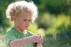 Kleiner blonder Junge, der mit einem kleinen Auto spielt Stockbilder