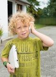 Kleiner blonder Junge, der mit einem Smartphone spielt Lizenzfreie Stockfotos