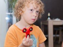 Kleiner blonder Junge, der mit Handspinner spielt Stockfotografie