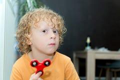 Kleiner blonder Junge, der mit Handspinner spielt Stockfoto
