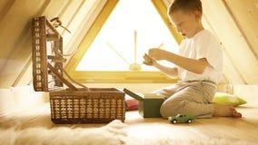 Kleiner blonder Junge, der mit seinen Spielwaren im Dachboden spielt stock video footage