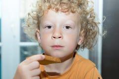 Kleiner blonder Junge, der morgens Brot isst Lizenzfreie Stockfotos
