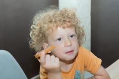 Kleiner blonder Junge, der morgens Brot isst Lizenzfreie Stockfotografie
