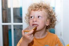 Kleiner blonder Junge, der morgens Brot isst Stockfotos
