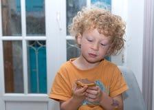 Kleiner blonder Junge, der morgens Brot isst Stockbilder