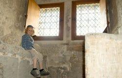 Kleiner blonder Junge, der nahe einem Fenster sitzt Stockfotos