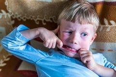 Kleiner blonder Junge der obenliegenden Ansicht, der dummes Gesicht auf Sofa macht Lizenzfreies Stockfoto
