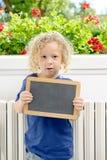 Kleiner blonder Junge, der Schultafel hält Stockfotografie
