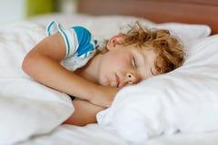 Kleiner blonder Junge, der in seinem Bett schläft Lizenzfreie Stockfotos