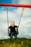 Kleiner blonder Junge, der Spaß am Spielplatz hat Lizenzfreie Stockbilder