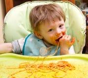 Kleiner blonder Junge, der Spaghettis isst Lizenzfreie Stockfotografie