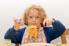 Kleiner blonder Junge, der Teigwaren mit Tomatensauce isst Lizenzfreies Stockbild