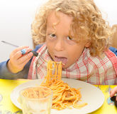 Kleiner blonder Junge, der Teigwaren mit Tomatensauce isst Stockfoto