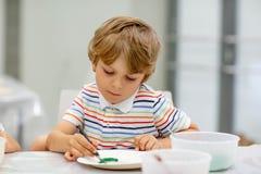 Kleiner blonder Junge, der unterschiedlichen Farben und das Malen mischt Lizenzfreies Stockfoto
