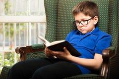 Kleiner blonder Junge, der zu Hause liest Stockfoto