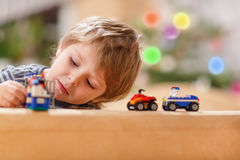 Kleiner blonder Junge, der zu Hause mit Autos und Spielwaren, Innen spielt. Stockfotografie