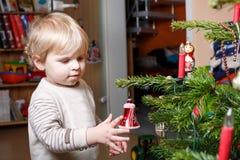 Kleiner blonder Junge, der zu Hause Weihnachtsbaum verziert. Stockfotos
