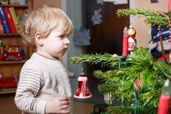 Kleiner blonder Junge, der zu Hause Weihnachtsbaum verziert. Stockfotografie