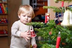 Kleiner blonder Junge, der zu Hause Weihnachtsbaum verziert. Lizenzfreies Stockbild