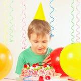 Kleiner blonder Junge in einem Feiertagshut, der den Geburtstagskuchen betrachtet Lizenzfreies Stockfoto