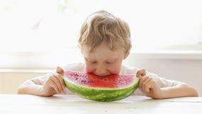 Kleiner blonder Junge genießt eine große Scheibe der Wassermelone stock video footage