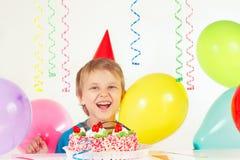 Kleiner blonder Junge im Feiertagshut mit Geburtstagskuchen und -ballonen Stockfotografie