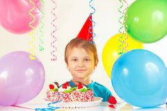 Kleiner blonder Junge im festlichen Hut mit Geburtstagskuchen und -ballonen Lizenzfreies Stockfoto